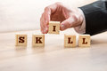 Businessman arranging blocks to form skill word close up hand wooden on top of the table Royalty Free Stock Photography