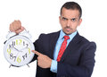 Businessman asian portrait of a young shows his finger to the big alarm clock isolated on white background Stock Image
