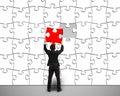 Businessman assembling unique red puzzle to white