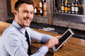 Businessman in bar handsome young man shirt and tie working on digital tablet and smiling while sitting at the counter Stock Images
