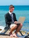 Businessman at the beach with noutbukom sevastopo l crimea Royalty Free Stock Image