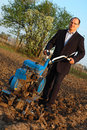 The businessman behind a tractor. Stock Photo