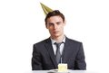 Businessman birthday portrait of calm in cap looking at camera with piece of cake in front of him Royalty Free Stock Images