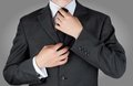 Businessman in black costume tie one's necktie Royalty Free Stock Photo
