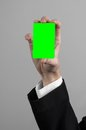 Businessman in a black suit and black tie holding a card a hand holding a card green card card is inserted the green chroma key Royalty Free Stock Photos