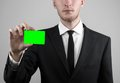 Businessman in a black suit and black tie holding a card a hand holding a card green card card is inserted the green chroma key Royalty Free Stock Image
