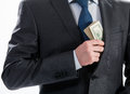 A businessman in a black suit putting money in his pocket closeup shot Stock Photography