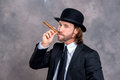 Businessman with bowler hat in black suit smoking big cigar Royalty Free Stock Photo