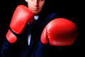 Businessman in boxing gloves isolated on black Stock Photography
