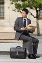Businessman with briefcase and newspaper on park bench, looking over shoulder Royalty Free Stock Photo