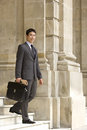 Businessman with briefcase and newspaper on steps, portrait, low angle view Royalty Free Stock Photo
