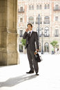 Businessman with briefcase and newspaper using mobile phone Royalty Free Stock Photo