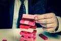 Businessman builds big tower with jenga bricks - retro style Royalty Free Stock Photo