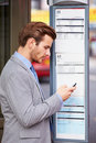 Businessman At Bus Stop With Mobile Phone Reading Timetable Royalty Free Stock Photo