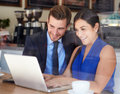 Businessman and businesswoman meeting in coffee shop looking at laptop Royalty Free Stock Image