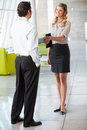Businessman And Businesswoman Shaking Hands In Office Stock Images