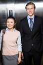 Businessman and businesswoman standing in an elevator Royalty Free Stock Photo