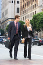 Businessman and businesswoman in street with takeaway coffee smiling Stock Image
