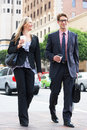 Businessman and businesswoman in street with takeaway coffee smiling Royalty Free Stock Images