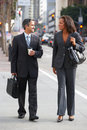 Businessman and businesswoman in street with takeaway coffee smiling Stock Photography