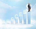 Businessman and businesswoman on the top of chart business office with success word Stock Photo