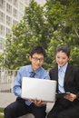 Businessman and businesswoman working together outdoors on the laptop Stock Photo