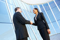 Businessman and businesswomen shaking hands outside office smiling to each other Stock Images