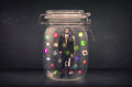 Businessman captured in a glass jar with colourful app icons con concept on background Royalty Free Stock Image