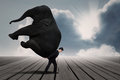 Businessman carry elephant by himself under blue sky Royalty Free Stock Photo