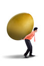 Businessman carrying big golden egg investment his back Stock Photo