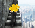 Businessman carrying gold puzzle piece climbing on old stairs Royalty Free Stock Photo