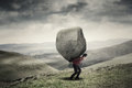 Businessman carrying rock at hill Royalty Free Stock Photo
