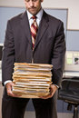 Businessman carrying stack of file folders Royalty Free Stock Image