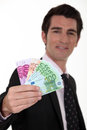 Businessman with cash a wad of Royalty Free Stock Photography