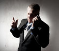 Businessman with a cellular phone serious Royalty Free Stock Photography