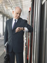 Businessman checking time by train in station mature an empty railway Stock Images