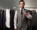 Businessman in classic vest against row of suits in shop Royalty Free Stock Photo
