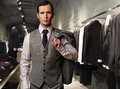 Businessman in classic vest against row of suits in shop Royalty Free Stock Image