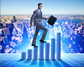 The businessman climbing bar charts in business concept