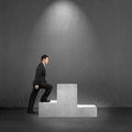 Businessman climbing on podium with spot lighting concrete background Stock Photo