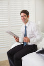 Businessman with coffee cup and newspaper at hotel room smiling young reading a Royalty Free Stock Photography