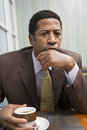Businessman with coffee cup in office portrait of a serious african american at table Royalty Free Stock Images