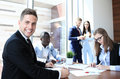 Businessman with colleagues in the background in office Royalty Free Stock Photo