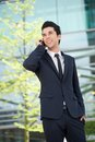 Businessman communicating on mobile phone outdoors portrait of a smiling Royalty Free Stock Image