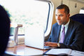 Businessman commuting to work on train and using laptop concentrating Stock Photo