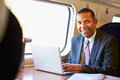 Businessman commuting to work on train and using laptop smiling Stock Photo