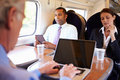 Businessman commuting to work on train and using laptop at table Stock Photography