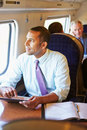 Businessman commuting on train using digital table tablet staring off camera Stock Photo