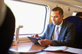 Businessman commuting on train using digital tablet working Stock Photo