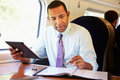 Businessman commuting on train using digital tablet working Royalty Free Stock Photos